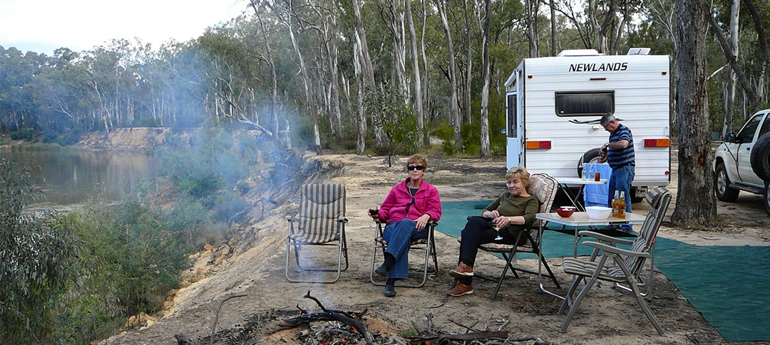 Two women are sitting on chairs to relax in front of their Newlands caravan