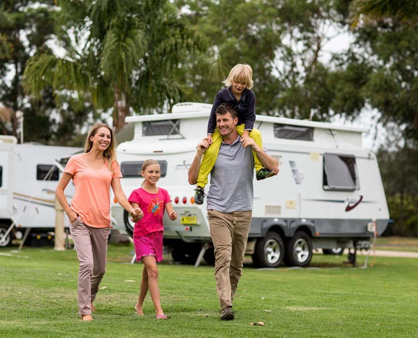 A happy family walking out of their caravan