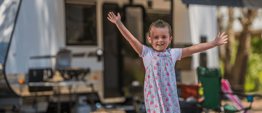 a happy kid in front of her family caravan